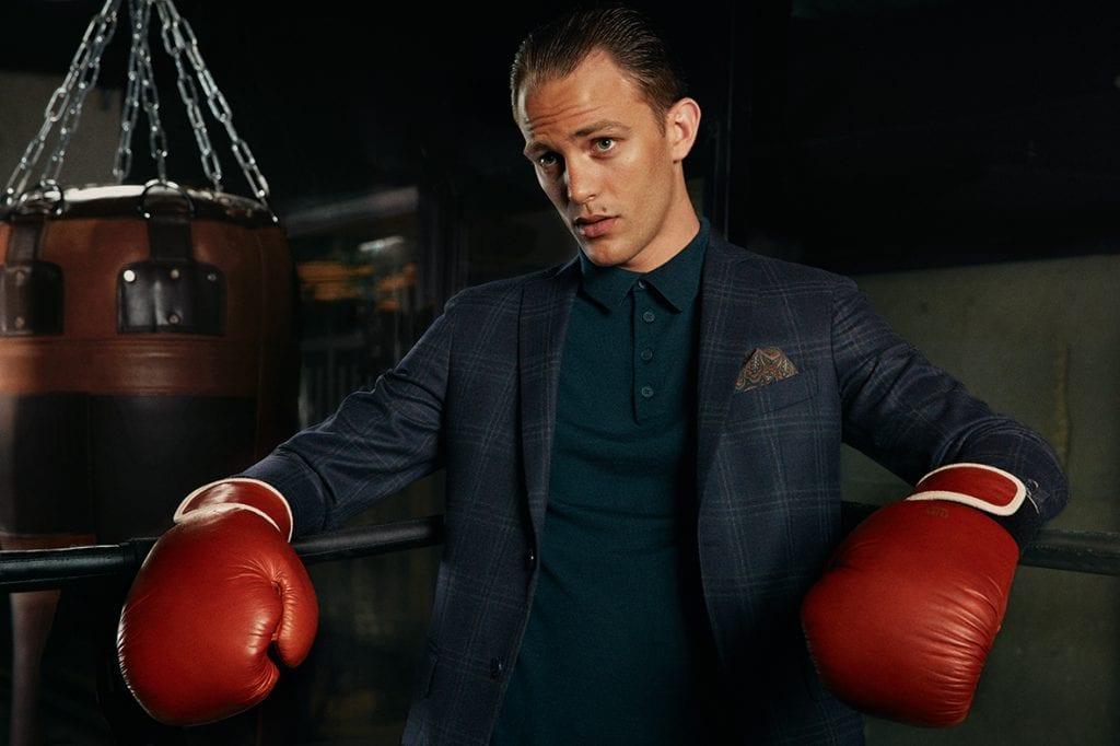 Le champion d'Europe de boxe thaï, égérie de la marque, porte ici un costume Bricklane en laine super 120, assorti à un polo Marco en laine mérinos et une pochette Winter baroque. (Photo Barrere & Simon)