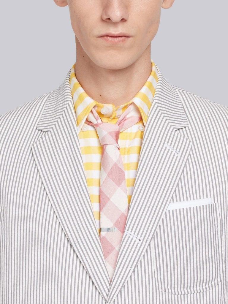 Seersucker et pince à cravate, deux incontournables du style Thom Browne, le créateur s'inspirant des codes preppy des années 60.